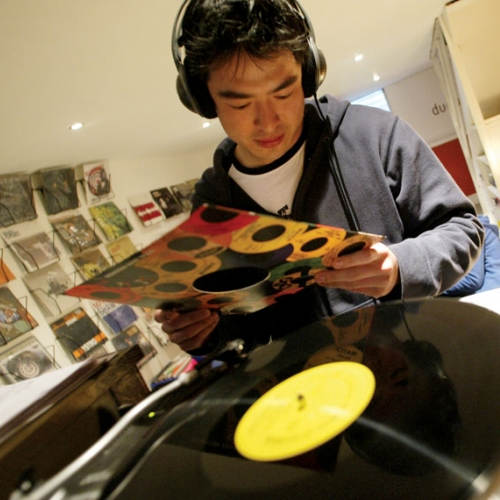 Student wearing earphones and putting record on record player.