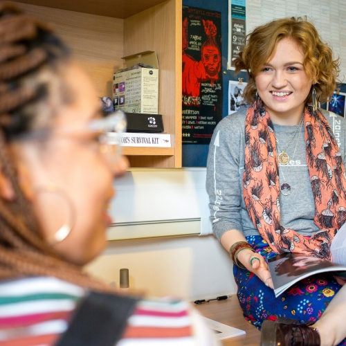 Student with book open on her lap chatting to another student in their room.