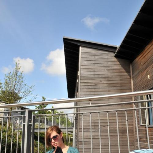 Student sat on balcony reading outside student accommodation.